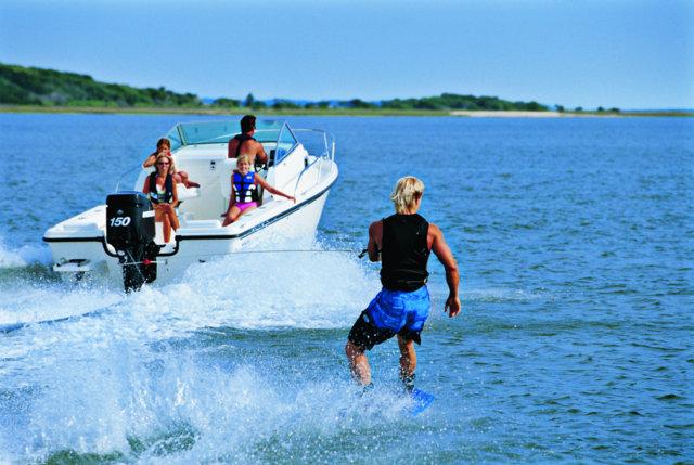 man wakeboarding behind boat